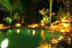backyard pool with lighting in he bushes