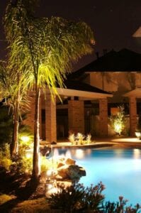 backyard with outdoor lighting around bushes and trees around a pool