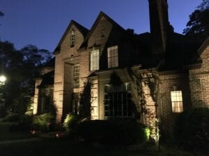 brick home with outdoor lighting