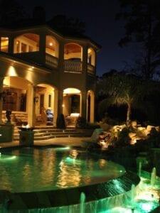 backyard patio lighting with pool and spa