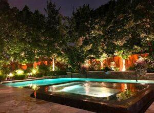 backyard pool with lit up plants