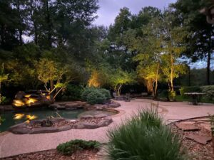 backyard with a pool being lit up with outdoorlighting
