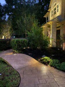 beautiful pathway to homes front door with outdoor lighting