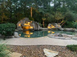 backyard pool with lights in the rock waterfall