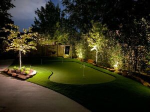 mini putting green at night surrounded by outdoor lighting