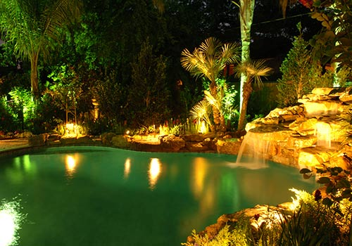 Beautiful free form swimming pool with waterfall and outdoor lights